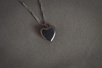 pendant in the shape of a heart on fabric background