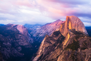 Half Dome Rock Yosemite National Park at Sunset.  Pink sky and clouds.