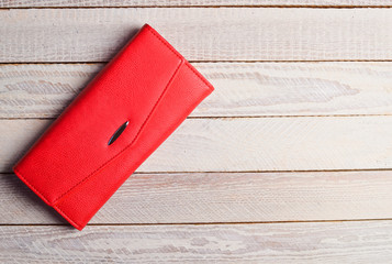 Red purse clutch on a white wooden table.