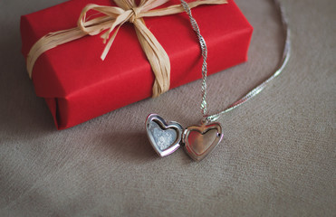 a gift and a pendant in the shape of a heart for Valentine's day