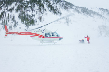 The helicopter landed people in the mountains in winter, raising