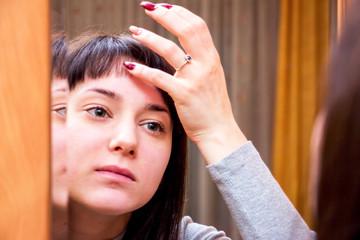 Pretty girl looking into mirror applying cream 4.