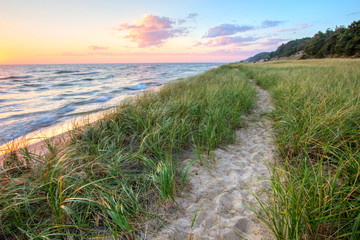 A Walk On The Beach. Sandy trail winds along a Great Lakes beach with a sunset horizon and sand dunes as a backdrop. Muskegon, Michigan.