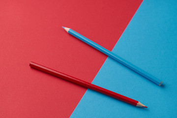 Colorful image of two pencils on red and blue background.  Office, school supply