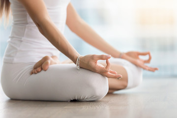 Young attractive yogi woman practicing yoga, sitting in Padmasana, exercise, Lotus pose with mudra, working out, wearing white sportswear, indoor, meditation session near window. Midsection close up Wall mural