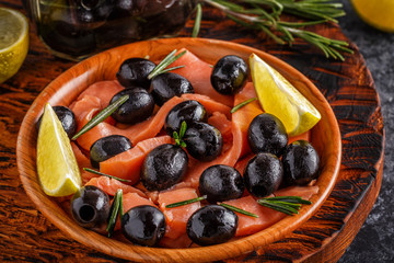 Salmon with olives and lime on a wooden board.