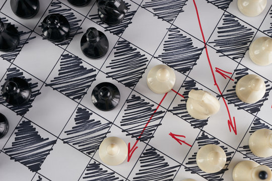 White strategy board with chess figures on it. Plan of battle. Close up, Top view