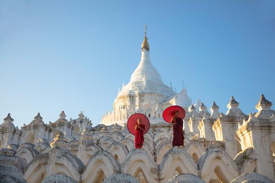 Asian monks sitting under umbrellas at historic temple, Mingun, Mandalay, Myanmar