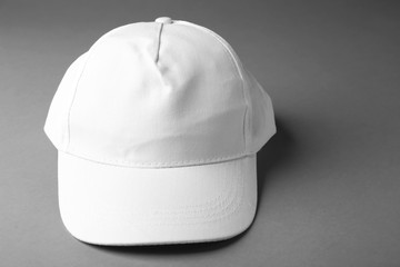 Blank white baseball cap on grey background