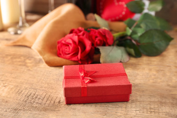St. Valentines Day concept. Gift box and beautiful roses on wooden table, closeup