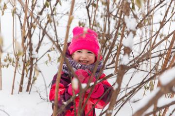 Little girl among winter bushes