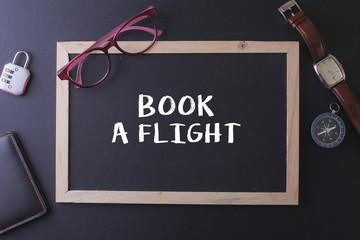 BOOK A FLIGHT WORD ON BLACKBOARD WITH WATCH,PASPORT, GLASS