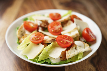 fresh homemade caesar salad with chicken and cherry tomatoes on wood table, shallow depth of field