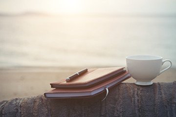 Notebooks,books, pen and a cup of coffee on the beach.