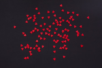 a lot of little red hearts on a black background.