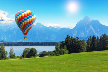 Poster Montgolfière / Dirigeable Scenic summer landscape with hot air balloon, lake and mountains
