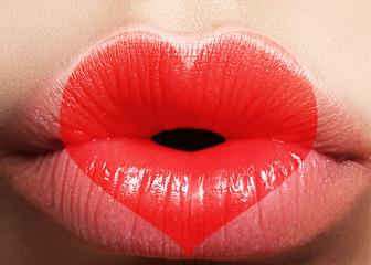 Valentine Heart on beautiful female Lips. Sweet Kiss. Love Makeup for Valntines Day. Cute Shape Heart like Symbol of Love. Celebrate Lip Make-up on macro shoot