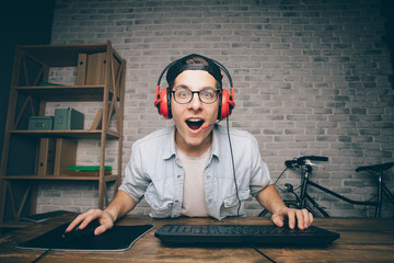 Young man playing game at home and streaming playthrough or walkthrough video