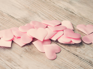 Pink hearts on textured wooden table. Valentine's mother day or baby birthday greeting card. Toned