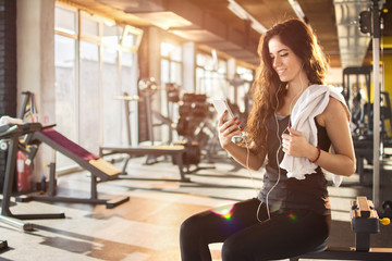Attractive girl with earphones listening to music on smartphone in gym.