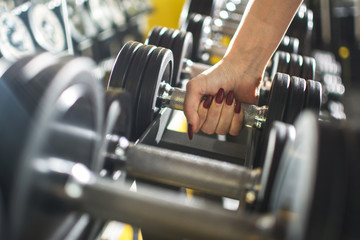 Close up of woman's hand holding dumbbell in gym.