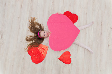 Sweet girl lying on the floor with decorations in the form of he