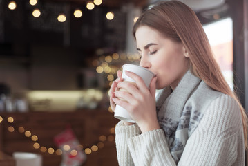beautiful caucasian woman drinking coffee at a cafe