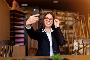 Beautiful young woman taking selfie at cafeteria.