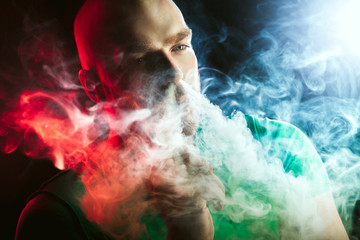 Men with beard  in sunglasses vaping and releases a cloud of vapor.Men with beard  in sunglasses vaping and releases a cloud of vapor.