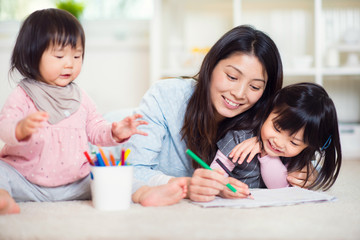 Happy japanese mother play with her two cute little daughters at