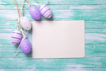 Easter or spring background. Decorative violet eggs and empty ta