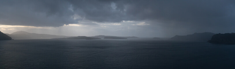 Rainy weather panorama over the sea. Rain on the water surface and stormy sky and clouds Wall mural