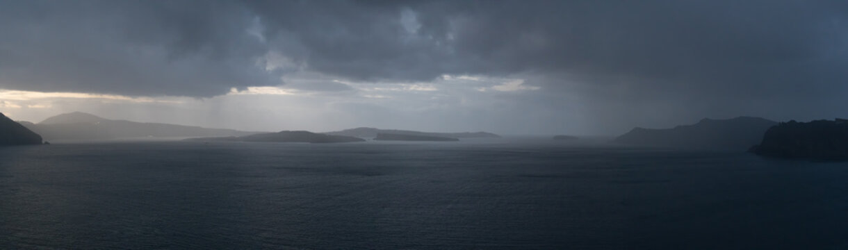 Rainy weather panorama over the sea. Rain on the water surface and stormy sky and clouds
