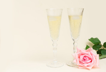 Pink blooming fresh valentines day roses on wood with two glasses of cold champagne with copy space