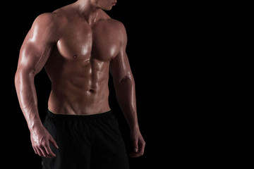 Muscular torso of male bodybuilder isolated. Cropped portrait of athlete with copy space on black background.