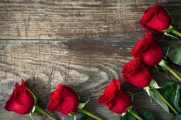 close-up red roses on old wooden background.
