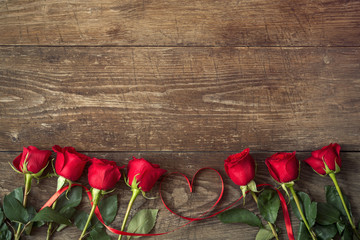 Close up on roses over wooden table with ribbon heart.