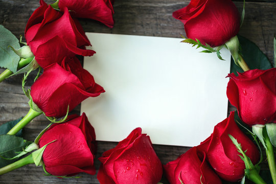 Red roses with empty card and copy space.