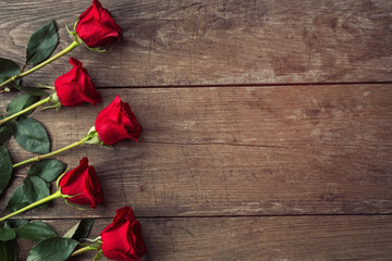 red roses on rustic wooden background.