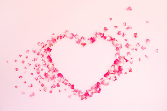 Shape of  heart made of dry pink roses petals on pink background. Valentine's card. Top view, flat lay.
