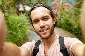 Stylish young bearded male blogger with backpack posing outdoors while recording video on front-facing camera of his gadget, addressing himself to his followers and telling them about his road trip
