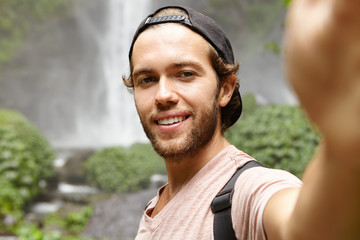 Human, nature and tourism. Handsome young traveler in snapback holding camera and smiling joyfully while taking selfie, posing by gorgeous waterfall in rainforest, having during journey during holiday