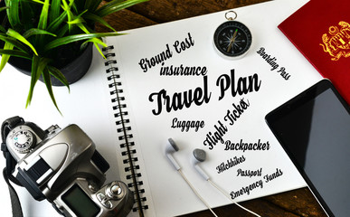 """Travel concept"" Top view info text on notepad with film camera,compass,passport,earphones and smart phone with wooden background."