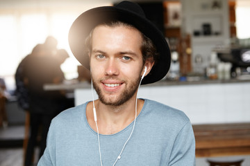 Human, leisure and modern technology concept. Indoor portrait of handsome young Caucasian freelancer smiling happily while relaxing at coffee shop and enjoying favourite tracks on headphones