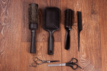 Four combs and two scissors on the wooden background