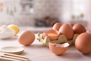 Fresh eggs on cartons with utensils in kitchen front view