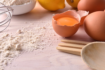 Fresh eggs flour and lemon with utensils on bench elevated