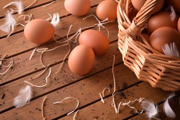 Freshly picked eggs in basket on wood table elevated view