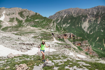 girl with a backpack and trekking poles walking at mountains