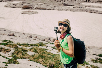 Woman traveler in summer mountains, video blogger concept